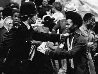 Homem negro diante de policial branco durante as revoltas raciais de Notting Hill. Fonte: Popular Resistence