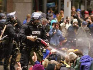Gás lacrimogênio é lançado por policial da tropa de choque contra um grupo de manifestantes antiglobalização durante os confrontos em Seattle. Foto: Steve Kaiser.