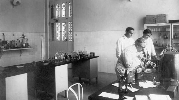 Oswaldo Cruz examina microscópio em laboratório de Manguinhos, observado por seu filho Bento Oswaldo Cruz e por Burle de Figueiredo