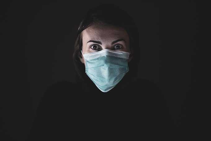 Fundo prevo e mulher em primeiro plano com máscara para se proteger da pandemia do novo coronavírus