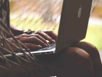 Homem segura laptop no colo.