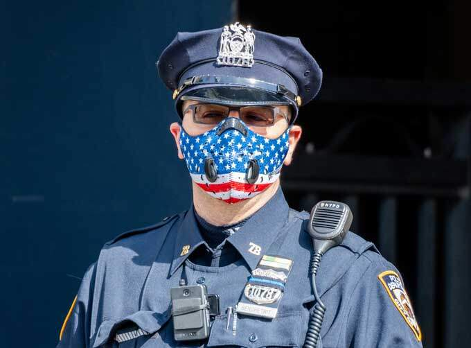 Policial usa máscara de proteção com estampa da bandeira americana no bairro do Brooklyn, em Nova York.