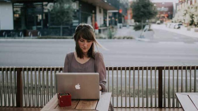 Mulher trabalha em seu computador.