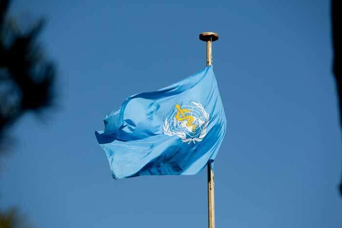 Bandeira da Organização Mundial da Saúde (OMS) tremula em mastro da entidade.